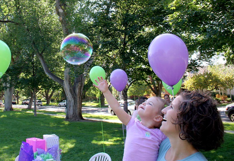 A feminine person holds a baby who is reaching for a bubble. They are in a park with trees, surrounded by balloons