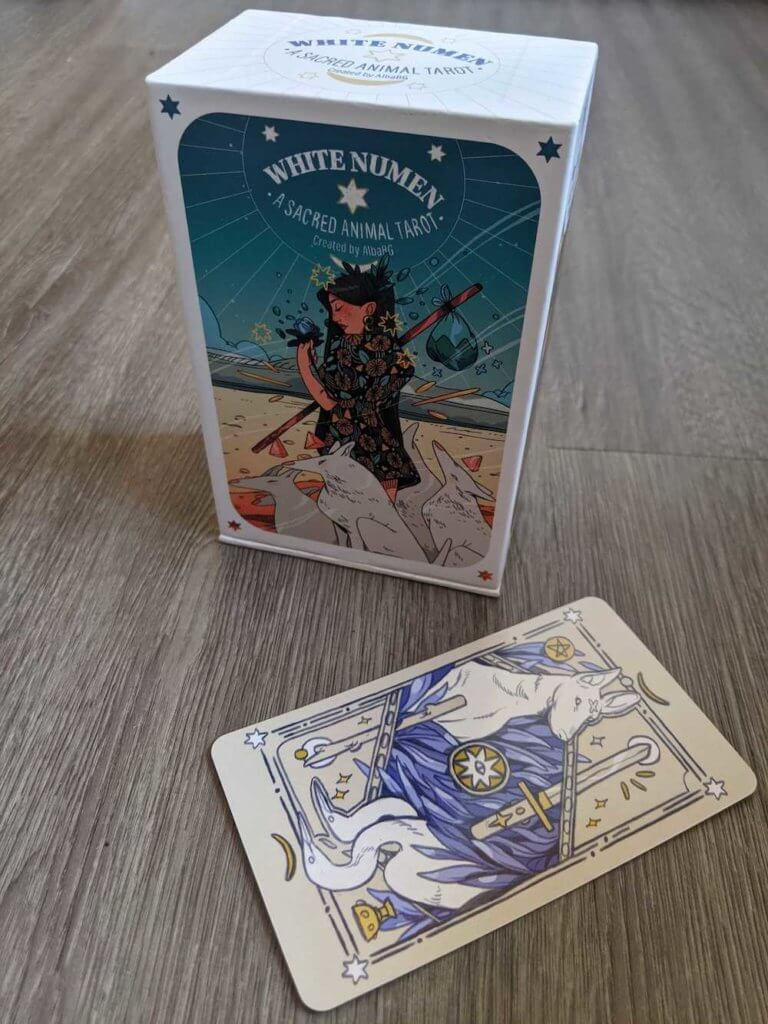 The box for the White Numen deck, featuring the art for the Fool, and the back of one of the cards, with a canine and 2 cranes