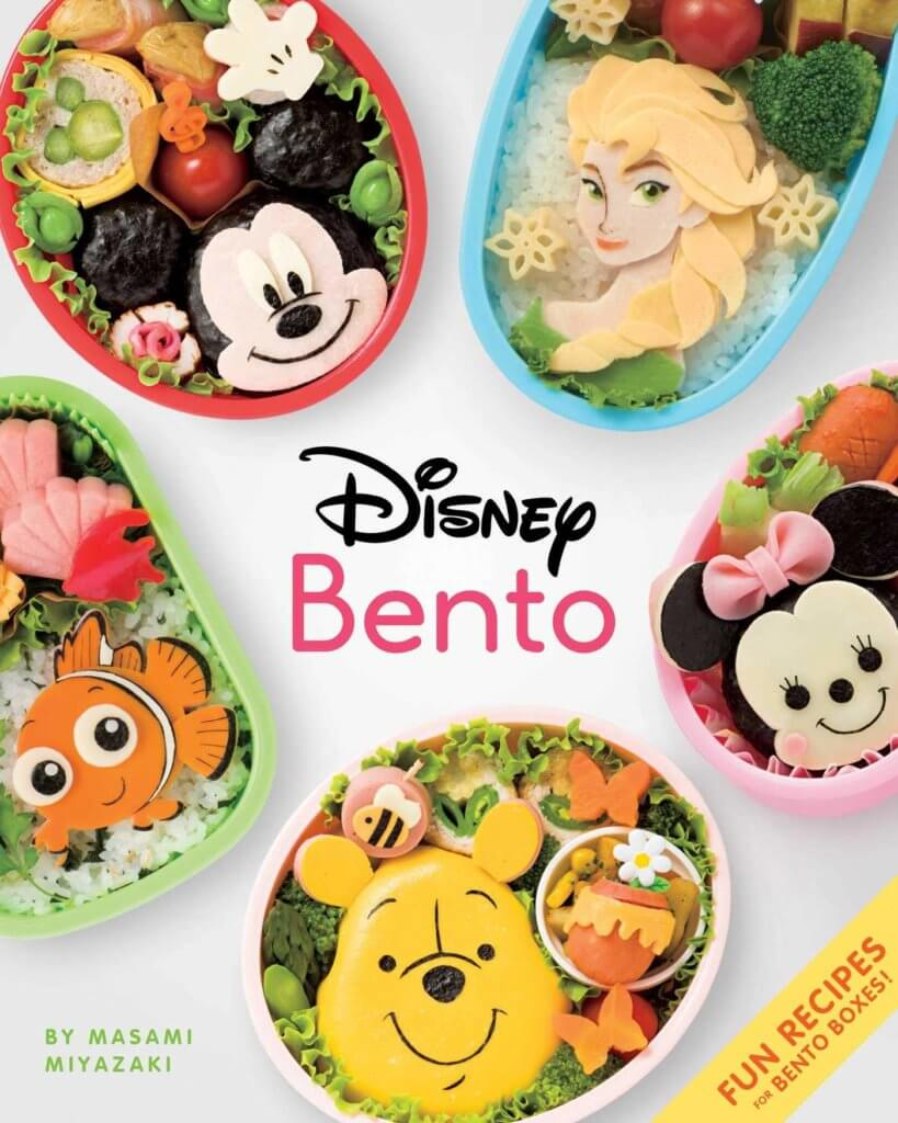 A close up of colorful bento dishes, five arranged in a circle, each representing a disney character. We see Mickey Mouse, Elsa from Frozen, Nemo from Finding Nemo, Minnie Mouse, and Winnie the Pooh