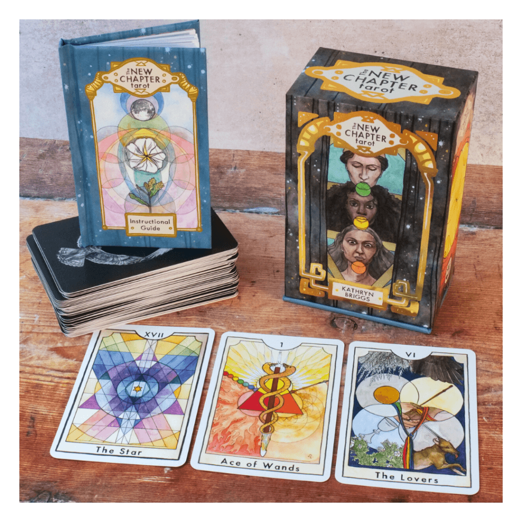 The New Chapter Tarot box and book pictured with three cards (the Star, Ace of Wands, the Lovers)
