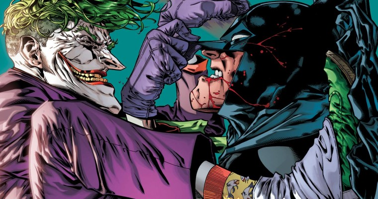 Joker squats on Batman's chest, menacingly looking down on him and knocking on his forehead with his fist as a bloodied Batman grits his teeth beneath his mask