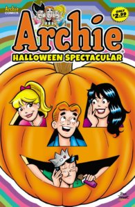 White teenagers Archie Andrews, Jughead Jones, Veronica Lodge and Jughead jones poke their heads through the eye and mouth holes of a giant Jack O'Lantern