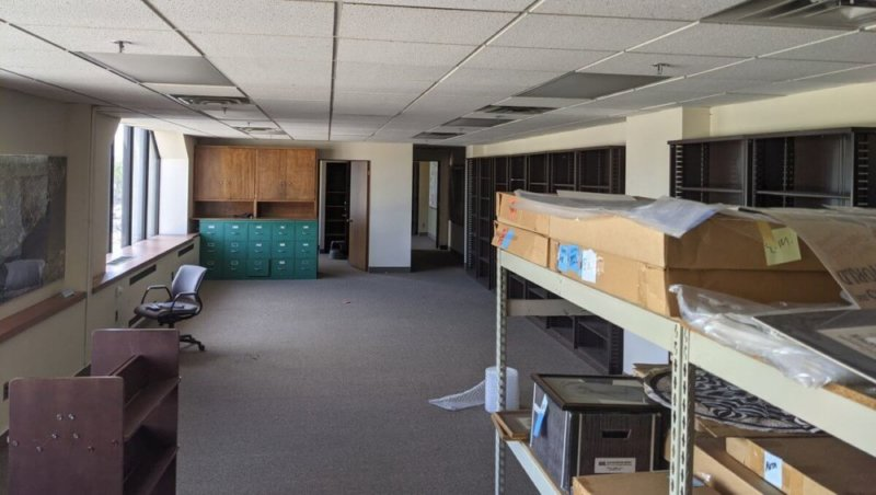 A photo of Diskette Press's new Detroit office. A spacious, gray-carpeted room houses filing cabinets and shelves for paper and print materials. On the left, a wide window with roomy counter space lets in bright sunlight.